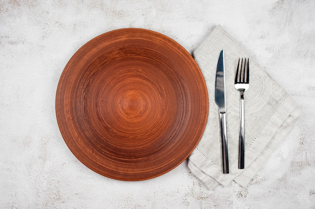 Empty plate and cutlery on a napkin. dinner setting, ceramic plate and silverware over light table.
