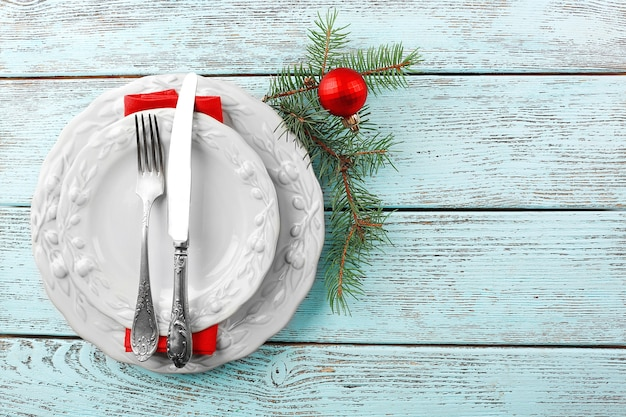 Empty plate, cutlery, napkin and glass on rustic wooden surface. christmas table setting concept