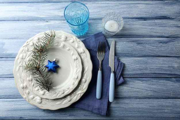 Empty plate, cutlery, napkin and glass on rustic wooden surface
