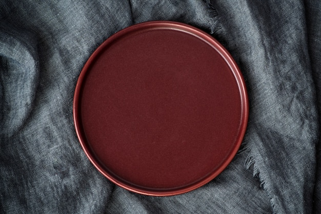 Empty plate on a dark gray background. top view, copy space