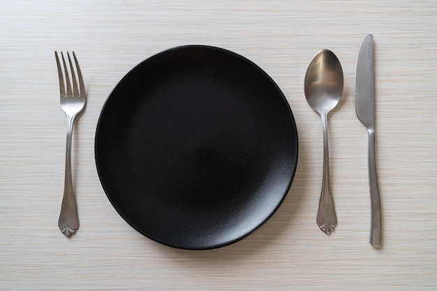Empty plate or dish with knife, fork and spoon on wood surface