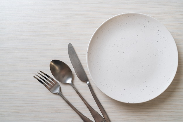 Empty plate or dish with knife, fork and spoon on wood table