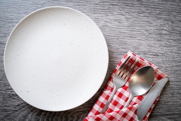 Empty plate or dish with knife, fork and spoon on wood tile background