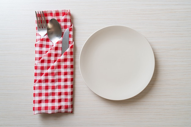 Empty plate or dish with knife, fork and spoon on wood tile table