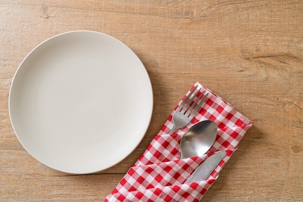 Empty plate or dish with knife, fork and spoon on wood tile