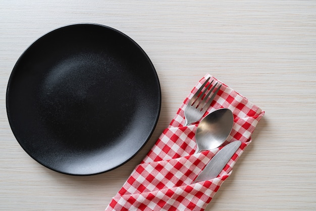 Empty plate or dish with knife, fork and spoon on wooden board