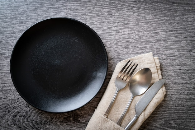 Empty plate or dish with knife, fork and spoon on wooden table