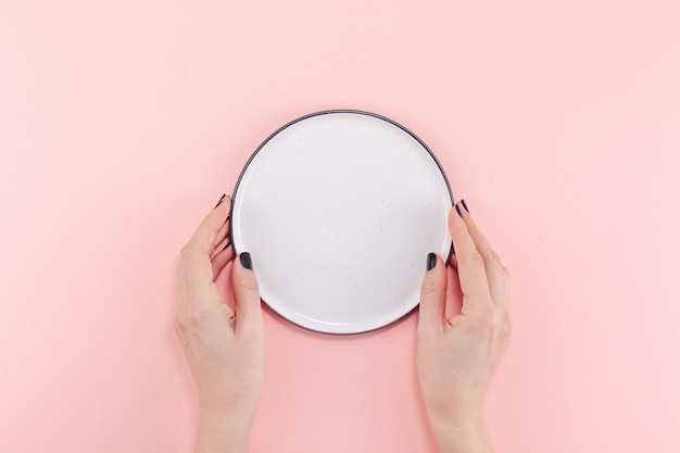 Empty plate in female hands