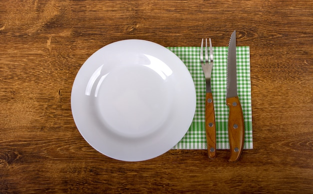 Empty plate, fork and knife on wooden.