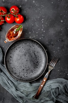 검은 배경 상위 뷰에 그레이비 보트에 빈 접시, 포크, 토마토, 기름