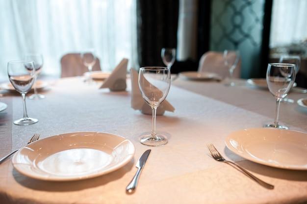 Пустая тарелка, стаканы и столовое серебро на деревянном столе