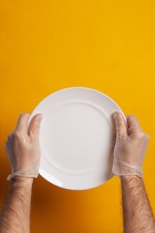 Пустую тарелку держат руками в защитных перчатках