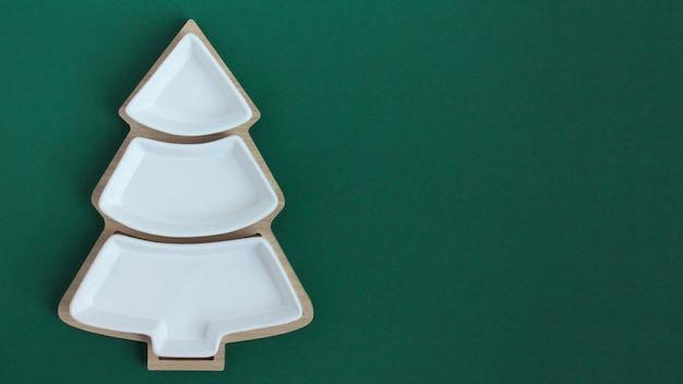 Пустая тарелка в форме елки на зеленом фоне. вид сверху.
