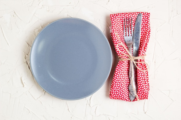 Empty plate, knife, fork and napkin over white table background. view from top with copy space.