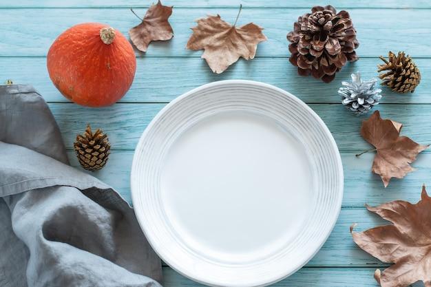 호박과 가을 장식이 있는 파란색 나무 탁자 위에 빈 접시가 올려져 있고, 위쪽 전망이 있습니다.