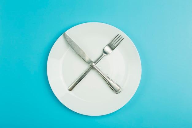 Пустая тарелка на синем минимальном фоне. пустая белая керамическая тарелка с ножом и вилкой на столе после еды.