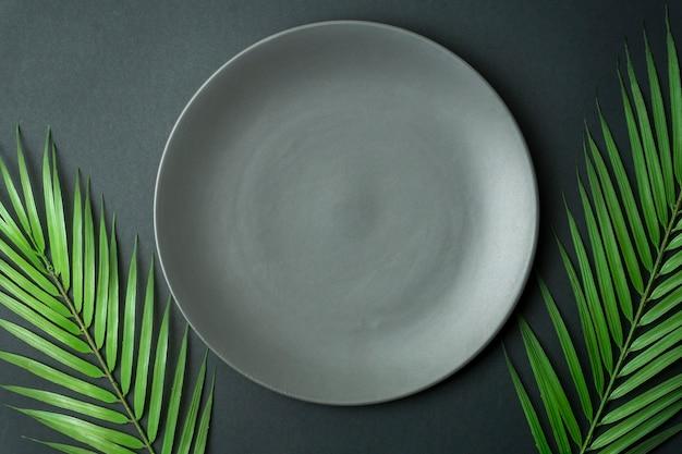 暗い背景に空のプレート。暗い美しい背景に食べ物と夕食のための空の灰色のセラミックプレート。
