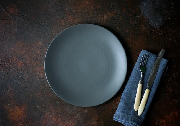 暗い背景に空のプレート。暗い美しい背景に食べ物と夕食のためのナイフとフォークで空の灰色のセラミックプレート。