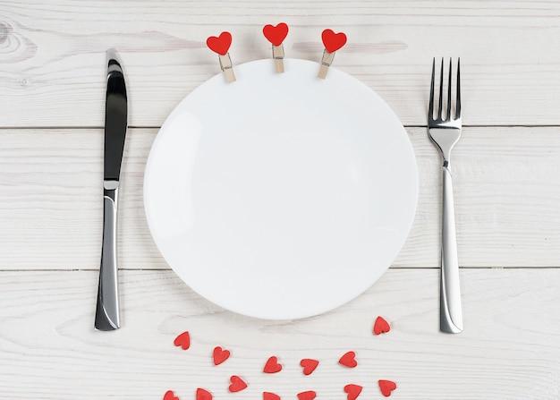 Пустая тарелка на белом деревянном фоне, украшенная сердечками на день святого валентина