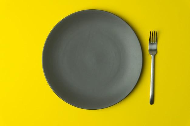 黄色の背景の空のプレート。食品と色の黄色の背景にディナーのフォークで空の灰色のセラミックプレート。