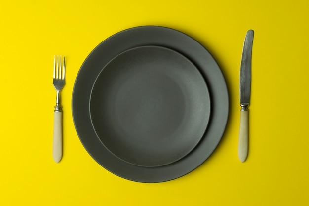 黄色の背景の空のプレート。食品と色の黄色の背景に夕食のためのナイフとフォークで空の灰色のセラミックプレート。