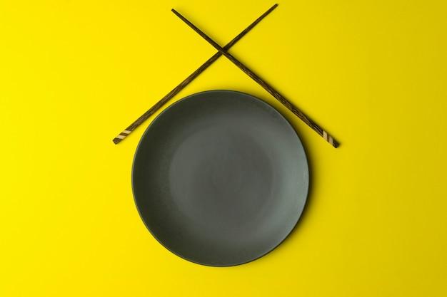 노란색 배경에 빈 접시입니다. 중국 젓가락으로 아시아와 중국 음식과 요리를위한 빈 접시