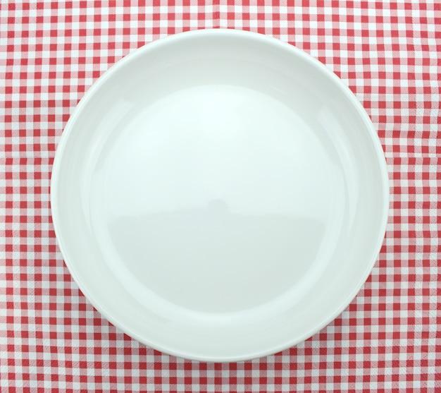 Пустая тарелка на клетчатой скатерти