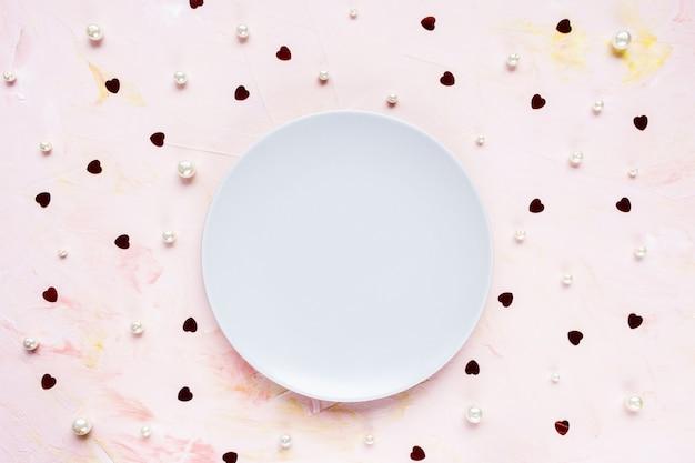 Пустая тарелка на розовом праздничном с украшением из красных сердечек
