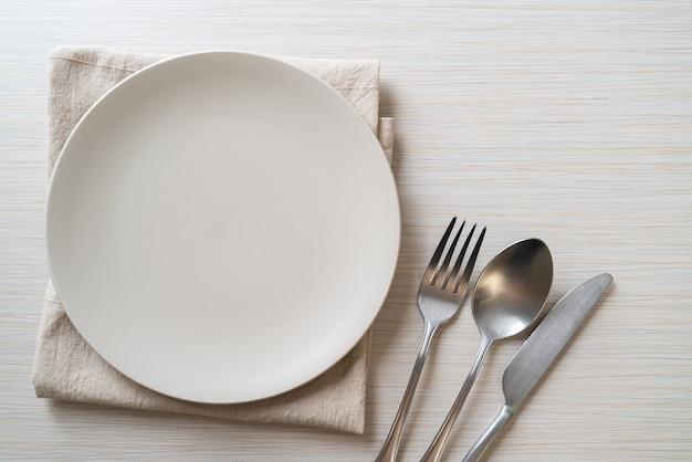 Пустая тарелка или блюдо с ножом, вилкой и ложкой на деревянной поверхности