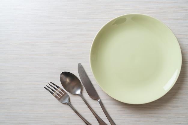 나무 타일 배경에 칼, 포크와 숟가락 빈 접시 또는 접시