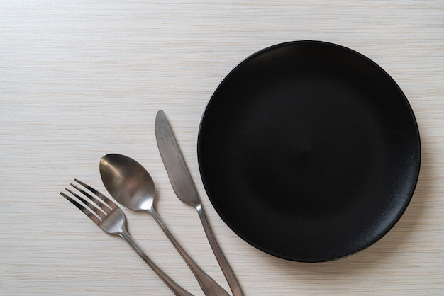 Пустая тарелка или блюдо с ножом, вилкой и ложкой на фоне деревянной плитки Premium Фотографии