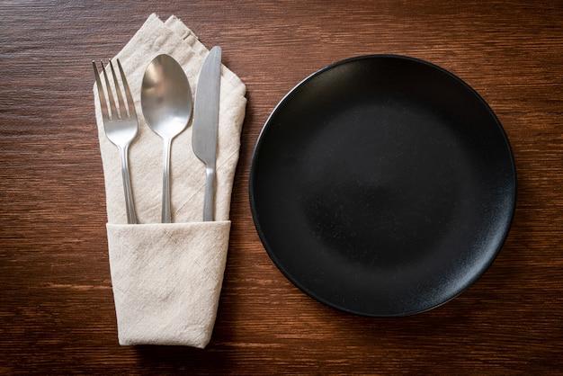 Пустая тарелка или блюдо с ножом, вилкой и ложкой на фоне деревянной плитки