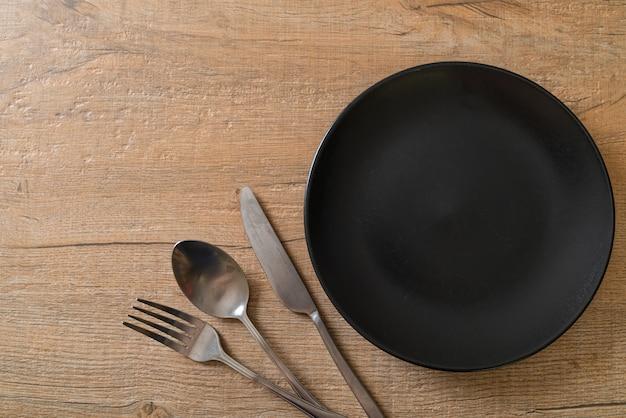 Пустая тарелка или блюдо с ножом, вилкой и ложкой на поверхности деревянной плитки