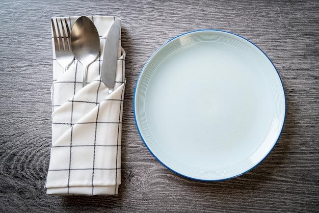 Пустая тарелка или блюдо с ножом, вилкой и ложкой на столе из деревянной плитки
