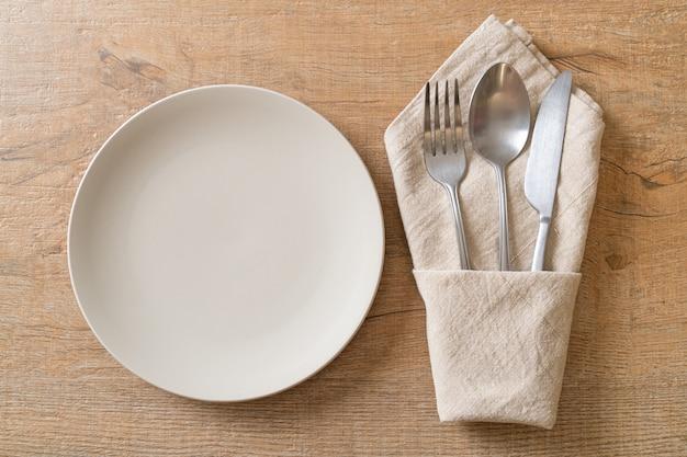 木製のテーブルにナイフ、フォーク、スプーンで空のプレートまたは皿
