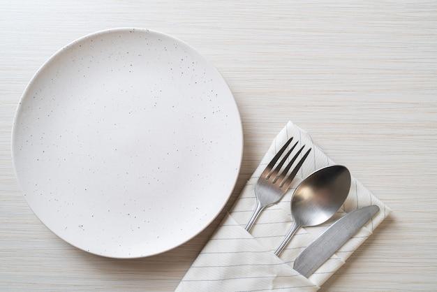 Пустая тарелка или блюдо с ножом, вилкой и ложкой на деревянном столе