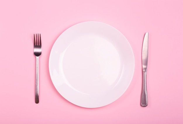 Empty plate on a pink background. white plate with knife and fork on a pink empty table.