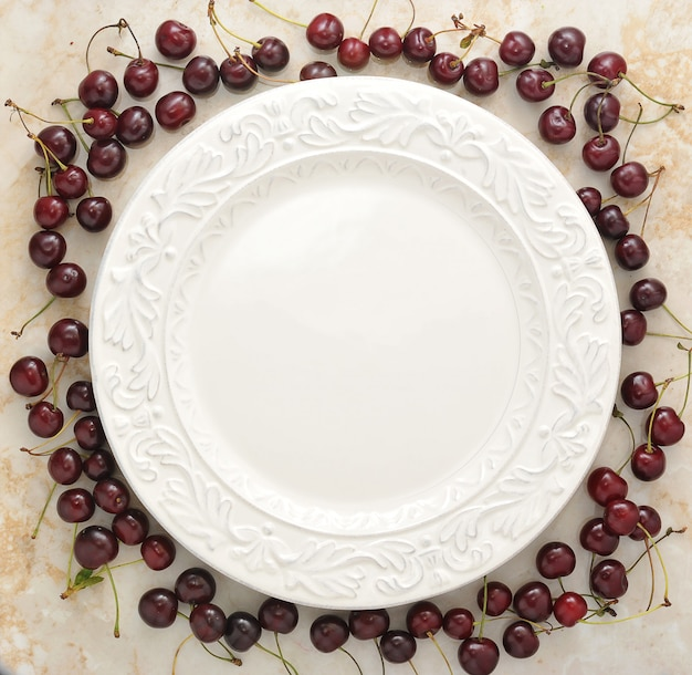 Empty plate and scattered around it cherries