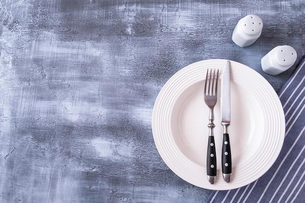 Пустая тарелка подается с вилкой и ножом. вид сверху, пространство для текста