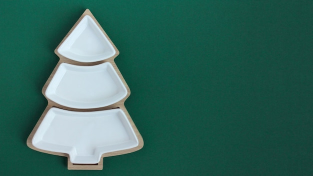 Empty plate in the shape of a christmas tree on a green background.the view from the top.