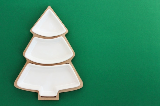 Empty plate in the shape of a christmas tree on a green background.