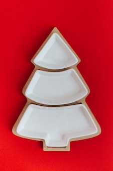 Empty plate in the shape of a christmas tree on a red background.the view from the top.