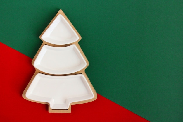 Empty plate in the shape of a christmas tree on a red and green background. three-section plate for appetizer or salad. the view from the top
