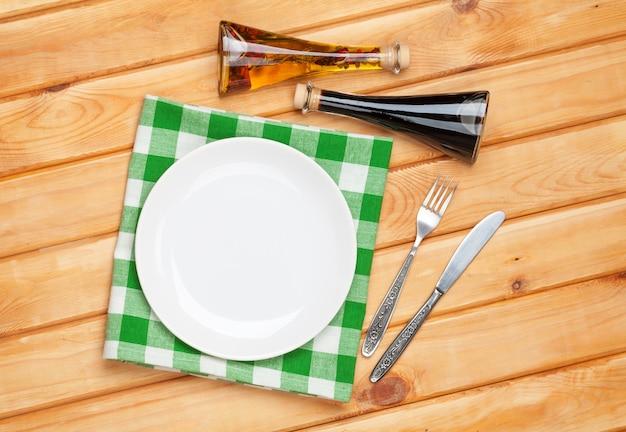 Пустая тарелка, столовое серебро и полотенце на фоне деревянного стола. вид сверху с копией пространства