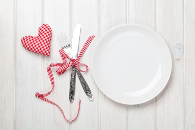 Empty plate, silverware and valentines day heart shaped toy. view from above over white wooden table