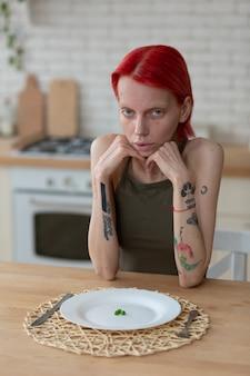 Пустая тарелка. худенькая рыжая женщина с анорексией сидит на кухне с пустой тарелкой