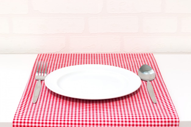 Empty plate and spoon fork on red and white checkered tablecloth