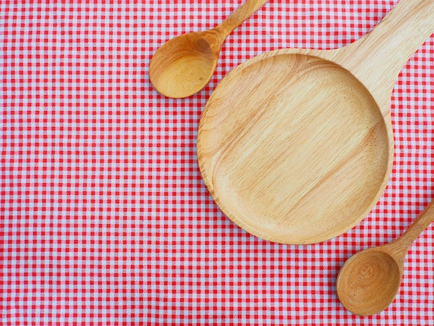 Empty plate and spoons on red checked tablecloth