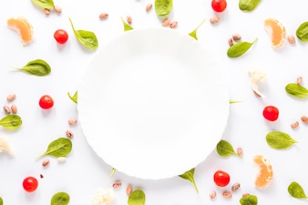 Empty plate surrounded by pinto bean; vegetables and orange slices arranged on white background