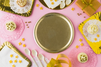 Empty plate surrounded with muffins on decorative pink background